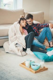 Entzückendes paar umarmt sich auf dem boden in der nähe der couch, bevor es müsli mit milch isst