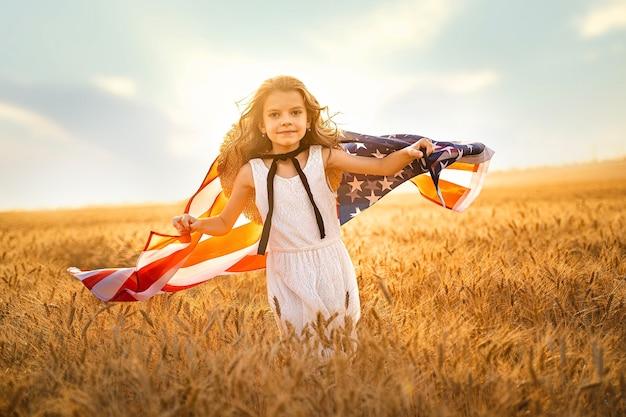 Entzückendes patriotisches mädchen im weißen kleid, das eine amerikanische flagge trägt