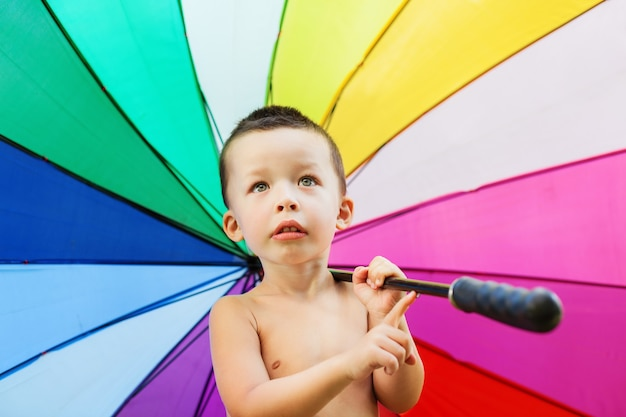Entzückendes porträt des glücklichen jungen, der in den händen hält und großen regenschirm mit lebendigem regenbogenfarbmuster dreht.