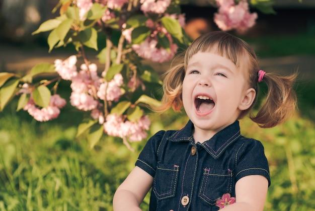 Entzückendes porträt des kleinen mädchens im garten, sakura-blüte