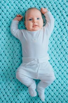Entzückendes reizendes neugeborenes männliches baby mit innenporträt des lebensstils der blauen augen von oben. nettes kind mit den prallen backen, die an liegen, ziehen sich im weißen pyjama auf woolen plaid des türkises zurück. lustige stillkindgefühle.