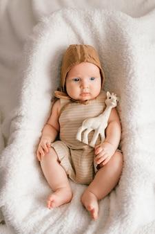 Entzückendes reizendes neugeborenes männliches baby mit lächelndem glücklichem gesichtslebensstilporträt von oben. lustiges kleinkind liegend mit spielzeug im korb bedeckt mit weißer tagesdecke.