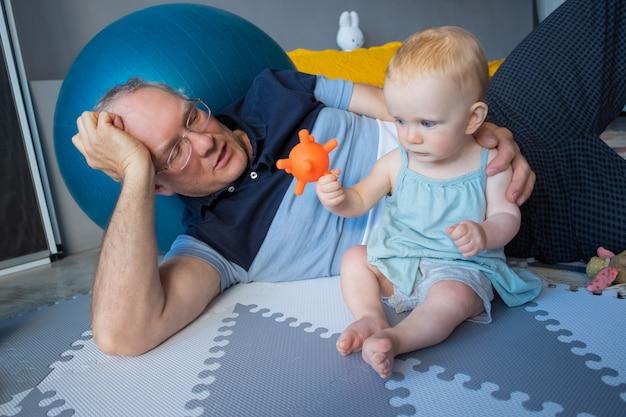 Entzückendes rothaariges neugeborenes, das auf boden sitzt und spielzeug spielt. glücklicher großvater in der brille und im blauen hemd, die nahe enkelkind liegen und geschichte erzählen. familien-, säuglings- und kindheitskonzept