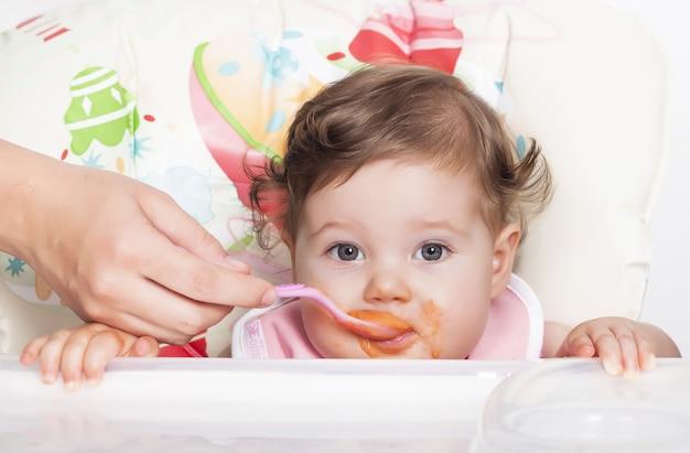 Entzückendes schmieriges weibliches baby, das ihr lieblingsessen isst