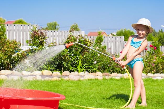 Entzückendes strömendes wasser des kleinen mädchens vom schlauch und vom lachen