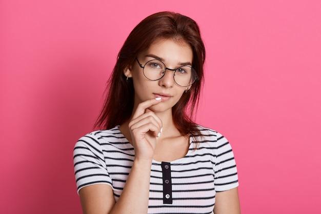 Entzückendes studentenmädchen, das gegen rosenwand mit nachdenklichem gesichtsausdruck aufwirft, gestreiftes t-shirt und brille trägt, finger auf lippen hält ,.