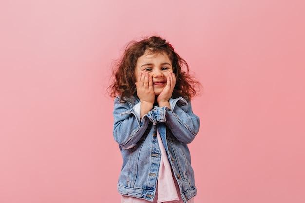 Entzückendes süßes kind in der jeansjacke, die gesicht berührt. lächelndes jugendliches mädchen, das auf rosa hintergrund aufwirft.