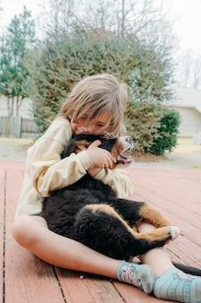 Entzückendes süßes kindermädchen, das mit haushunden sitzt und den kleinen berner welpen auf der veranda umarmt