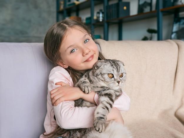 Entzückendes süßes lächelndes mädchen, das schottische graue katze auf dem sofa zu hause umarmt haustiere freundschaft zu hause