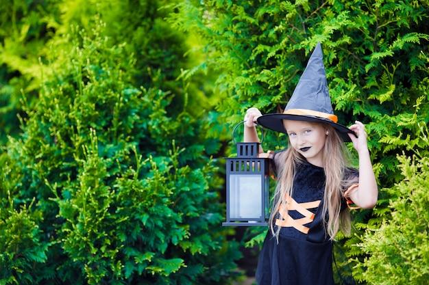 Entzückendes tragendes hexenkostüm des kleinen mädchens mit besen auf halloween draußen