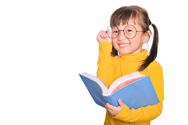 Entzückendes und fröhliches asiatisches kleines mädchen, das eine brille trägt, die interessantes buch liest, das an der bildung beteiligt ist, die auf weiß isoliert wird