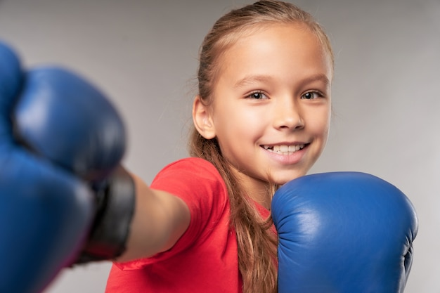 Entzückendes weibliches kind in boxhandschuhen, das luft stanzt und lächelt, während es vor grauem hintergrund steht