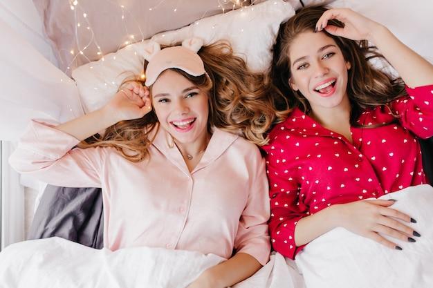 Entzückendes weißes mädchen im roten schlafanzug, der unter decke mit lächeln liegt. glückseliges weibliches modell mit lockiger frisur, die im bett mit schwester entspannt.
