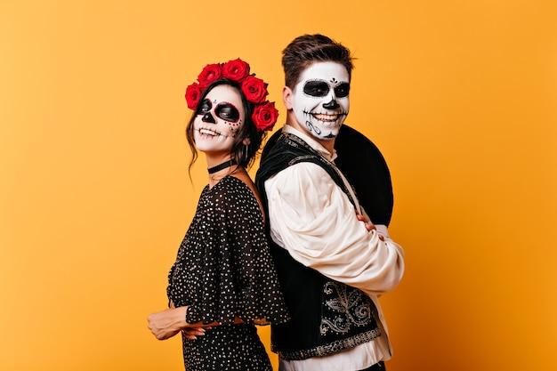 Entzückendes zombiemädchen im rosenkranz, der auf gelber wand aufwirft. glückliches paar mit muerte make-up, das spaß in halloween hat.