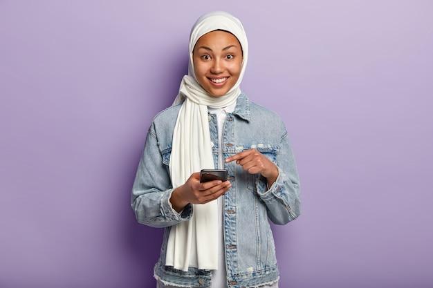 Entzückte junge muslimische frau, die mit ihrem telefon aufwirft