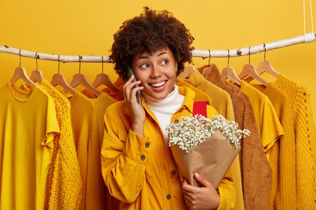 Entzückte lockige frau wendet sich ab, ruft per handy an, teilt eindrücke nach dem einkaufstag, posiert mit blumenstrauß