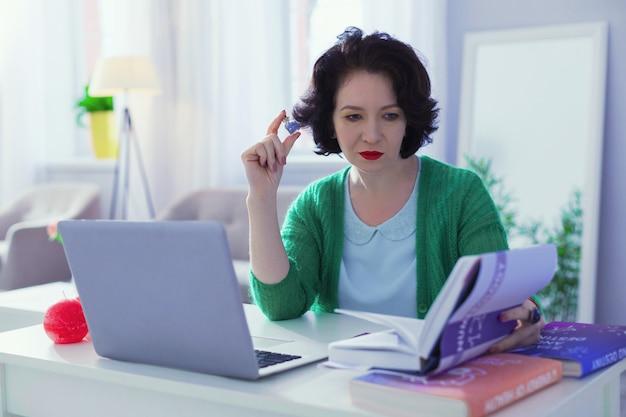 Enzyklopädie der zahlen. kluge, gut aussehende frau, die eine enzyklopädie von zahlen liest, während sie vor dem laptop sitzt