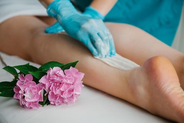 Epilierungsmeister trägt wachspaste mit einer hand in blauen handschuhen mit einer blume in der nähe auf die beine auf.
