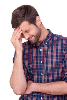 Episches scheitern. frustrierter junger mann in freizeithemd, der seine stirn mit der hand berührt und die augen geschlossen hält, während er isoliert auf weiß steht