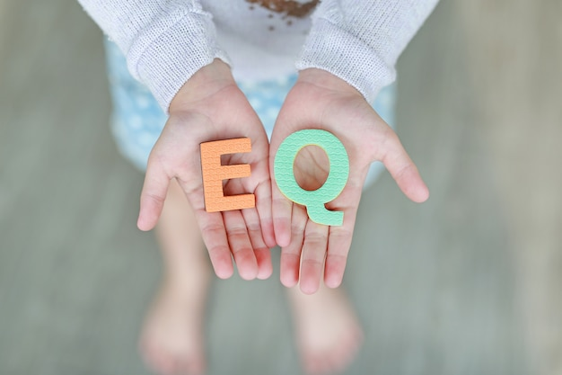 Eq (emotional quotient) schwammtext auf kinderhänden.