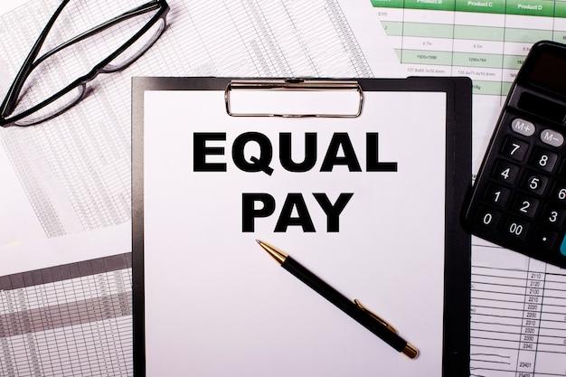 Equal pay wird auf ein weißes blatt papier in der nähe der brille und des taschenrechners geschrieben