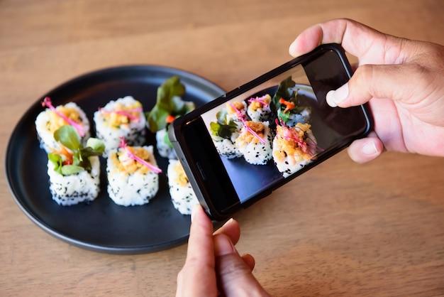 Er benutzt ein handy und macht ein foto von sushi, das vor einem japanischen restaurant platziert wird.