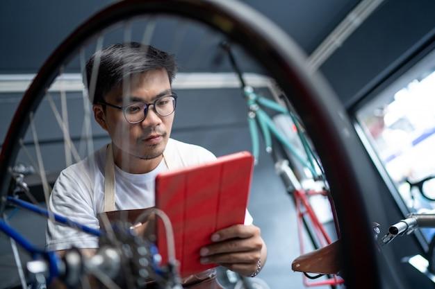 Er benutzt eine tablette, um das produkt zu überprüfen. der eingang des fahrradladens kümmert sich um die fahrräder der kunden, um den zustand zu überprüfen.