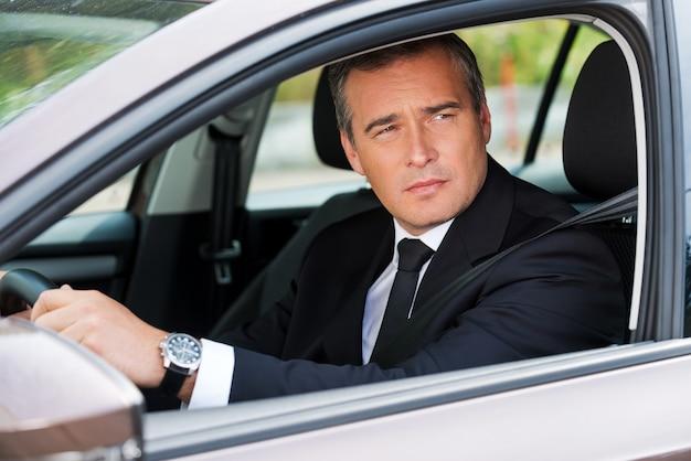 Er fährt sein neues auto. selbstbewusster reifer geschäftsmann, der auto fährt und wegschaut