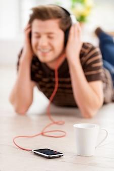 Er genießt seine lieblingsmusik. glücklicher junger mann mit kopfhörern, der musik hört und die augen geschlossen hält, während er in seiner wohnung auf dem boden liegt