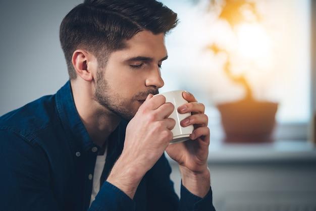 Er genießt seinen frischen kaffee. nahaufnahmeteil des hübschen jungen mannes, der kaffee trinkt