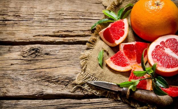 Er grapefruit auf alten stoff mit blättern und messer auf holztisch geschnitten.