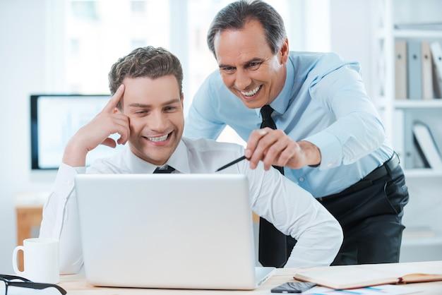 Er hilft ihm bei seiner arbeit. zwei fröhliche geschäftsleute in abendgarderobe diskutieren etwas discuss