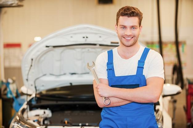 Er ist bereit zu arbeiten. selbstbewusster junger mann in uniform, der einen schraubenschlüssel hält und lächelt, während er in der werkstatt mit dem auto im hintergrund steht