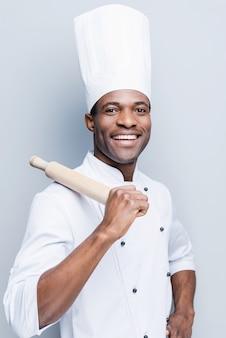 Er ist ein meister in der küche. fröhlicher junger afrikanischer koch in weißer uniform