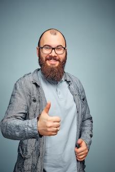 Er lebensstil eines erfolgreichen jungen mannes mit brille, bart, modische jeansjacke zeigt daumen hoch