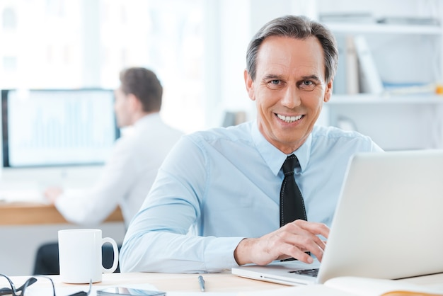 Er lebt in dieser arbeit. glücklicher geschäftsmann in formeller kleidung, der am laptop arbeitet und in die kamera lächelt Premium Fotos