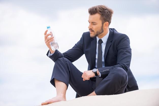 Er muss sich erfrischen. deprimierter junger geschäftsmann, der eine flasche mit wasser hält und sie beim sitzen auf sand betrachtet