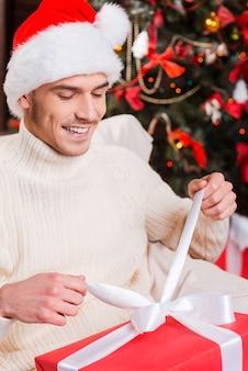 Er öffnet sein weihnachtsgeschenk. blick von oben auf den hübschen jungen mann mit weihnachtsmütze, der die geschenkbox öffnet und mit dem weihnachtsbaum im hintergrund lächelt