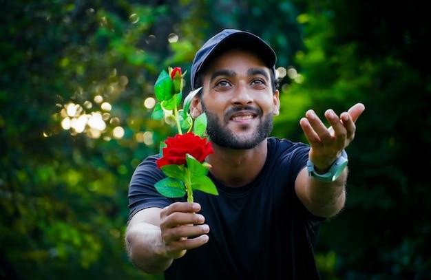 Er schlägt seiner freundin mann mit schöner roter rose vor, die dem mädchen gibt und seine hand gibt