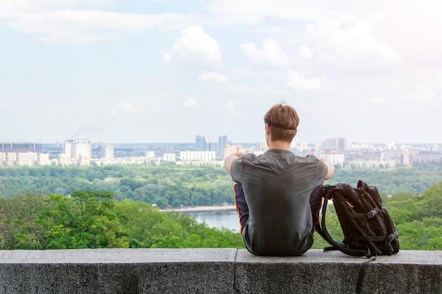 Er sitzt alleine mit einem rucksack mit blick auf die stadt