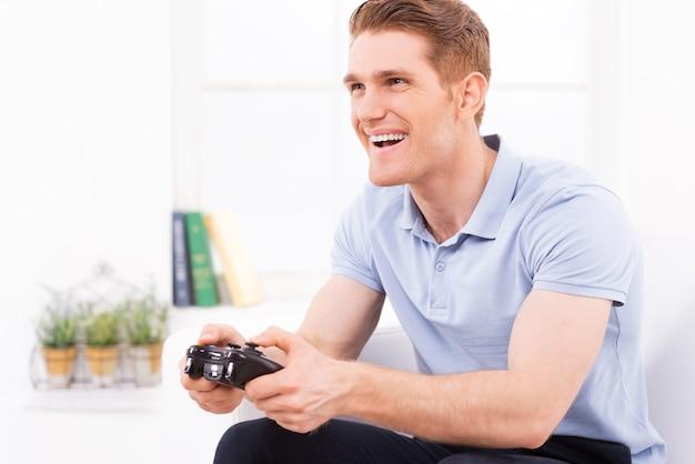 Er spielt sein lieblingsvideospiel. glücklicher junger mann mit joystick beim spielen von videospielen zu hause