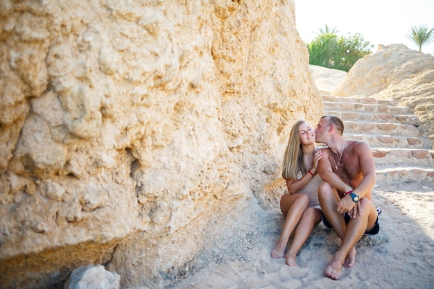 Er und sie sind am strandsand, sonne. paar sitzt am meer, liebe, zärtlichkeit, urlaub