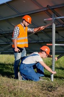 Erbauer, die rahmen mit sonnenkollektoren auf schraubenförmigen stapel installieren.