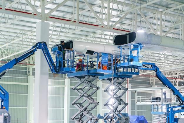 Erbauer-schlosser installieren hvac-kanalreinigungs- und belüftungsrohre, die von der decke hängen