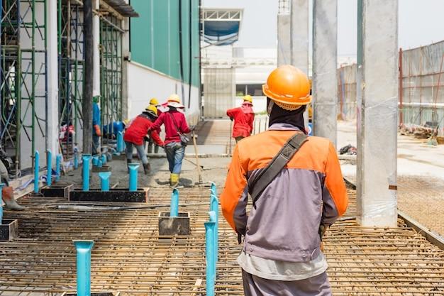 Erbauerarbeitskraft mit strömendem beton der boompumpe auf metallstangenverstärkung der verschalung