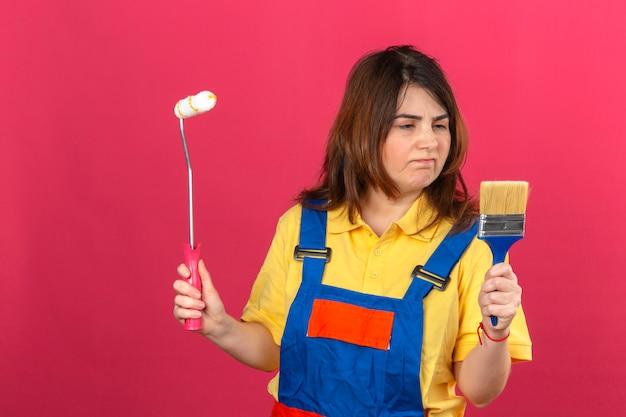 Erbauerfrau, die bauuniform trägt, die farbroller und pinsel hält, die es mit traurigem ausdruck betrachten, der über isolierte rosa wand missfällt