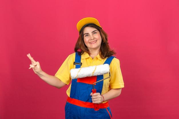 Erbauerfrau, die bauuniform und gelbe kappe hält, die farbroller hält, der fröhlich nummer drei mit den fingern über isolierter rosa wand zeigt