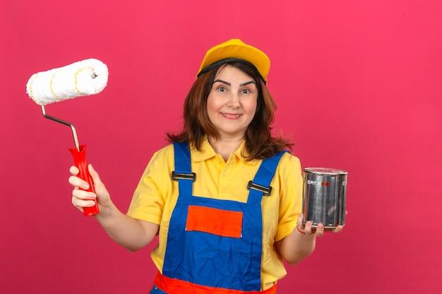 Erbauerfrau, die bauuniform und gelbe kappe trägt, die farbroller und farbe hält, kann mit glücklichem gesicht über isolierter rosa wand lächeln