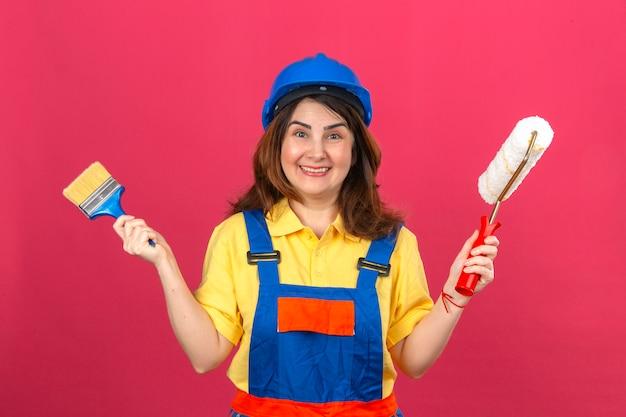 Erbauerfrau, die bauuniform und sicherheitshelm hält, die pinsel und farbroller in den händen hält, die fröhlich über isolierte rosa wand lächeln