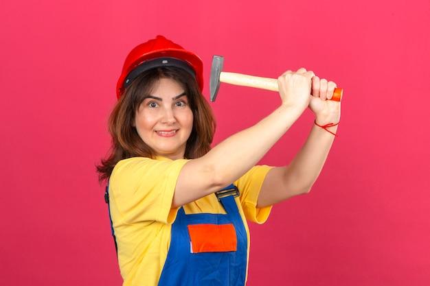 Erbauerfrau, die bauuniform und sicherheitshelm mit lächeln trägt, das droht, mit hammer zu schlagen, der spaß über isolierter rosa wand hat